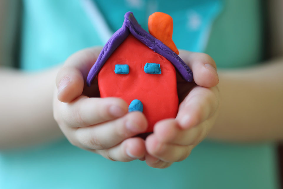 Little kid holding a playdough house with their hands.