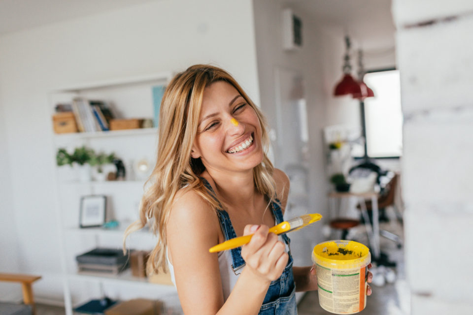 Women smiling as she paints her home