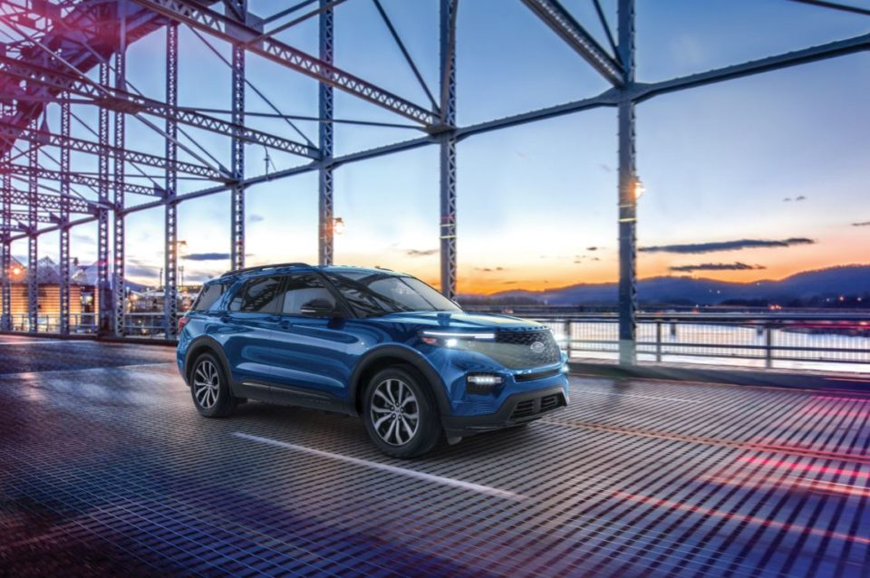 Blue Ford Explorer on bridge at sunset