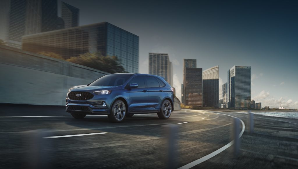 Blue Ford Edge on road before city background
