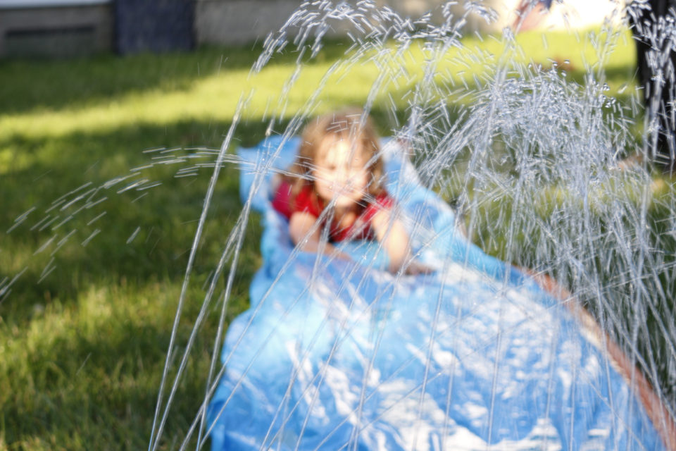 Smiling girl sliding down an outdoor slip and slide