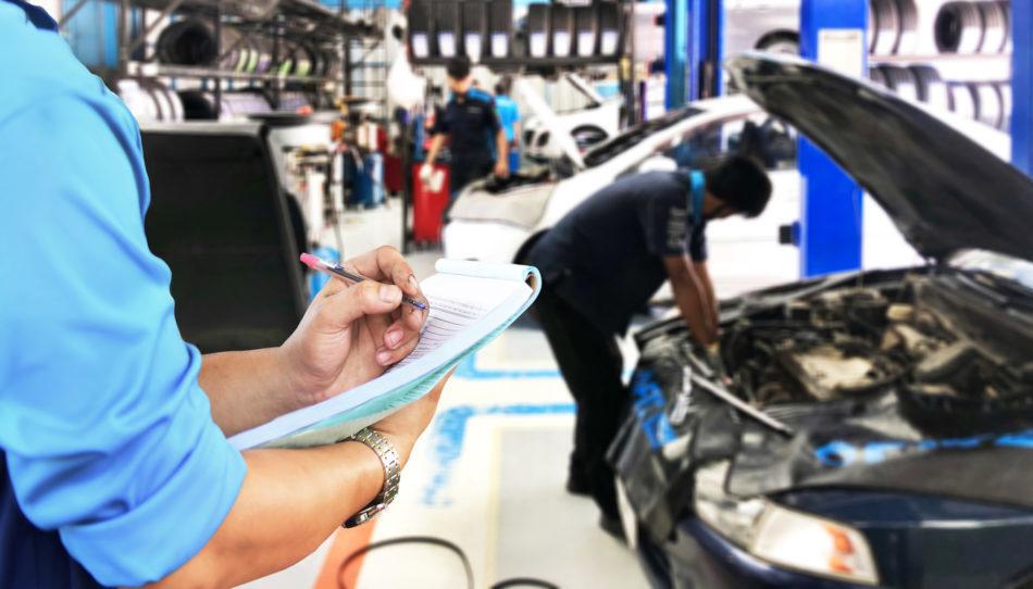 Mechanic checks the engine repair list at the garage.
