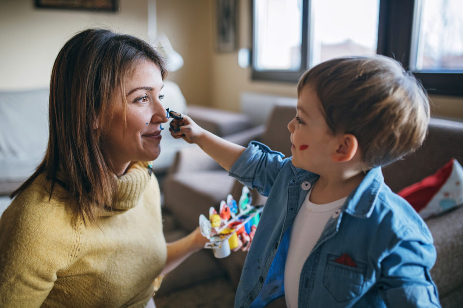 Little boy painting his mother with finger paint