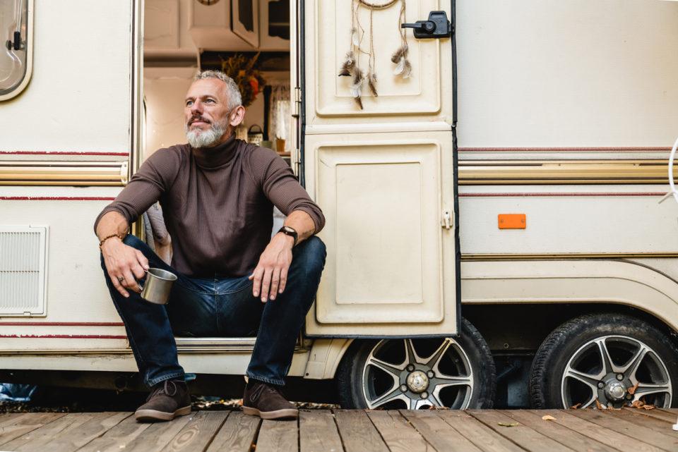 senior man with a beard sitting on the doorstep of the motor home holding iron mug